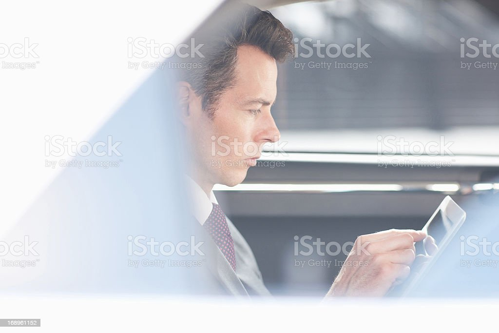 Businessman using tablet computer in backseat of car stock photo