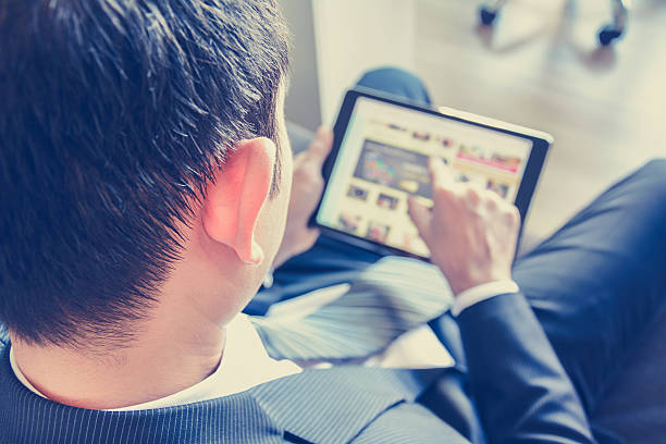 Businessman using tablet computer while sitting on the couch stock photo
