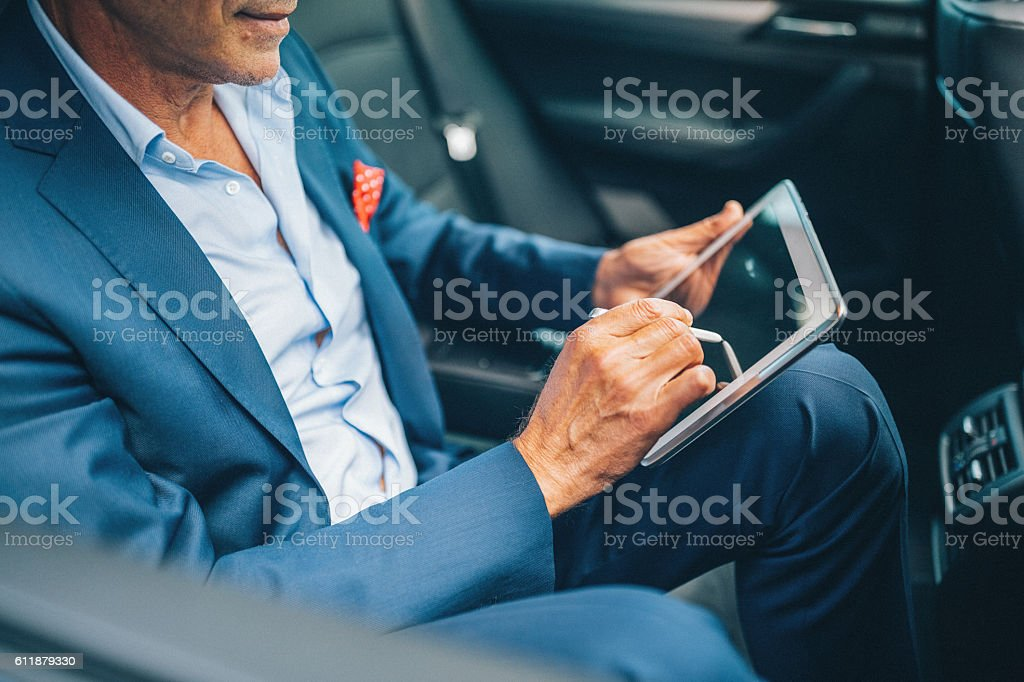 Businessman using tablet pc in car stock photo