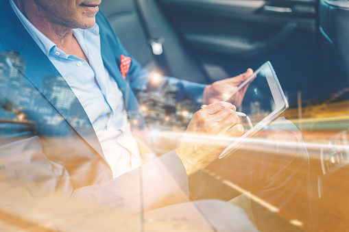 istock Businessman using tablet pc in car 612239458