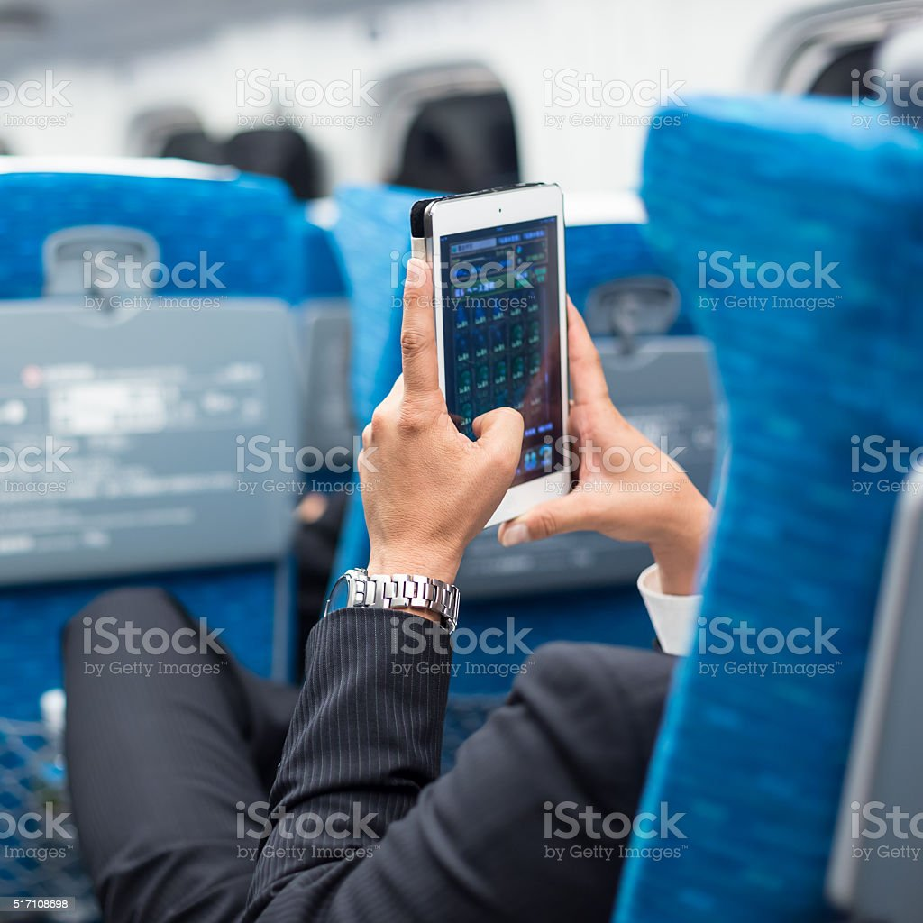 Businessman using tablet phone on airplane. stock photo