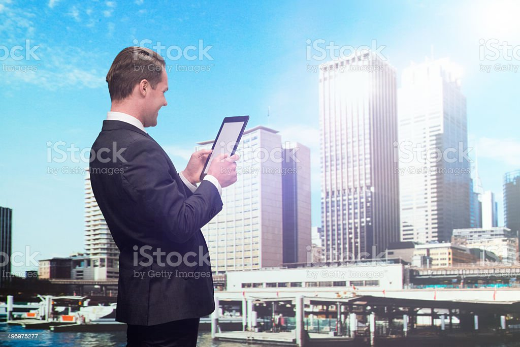 Businessman using tablet & standing in front of city royalty-free stock photo
