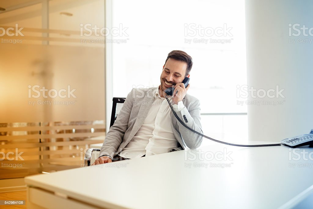 Businessman using talking on phone in office stock photo