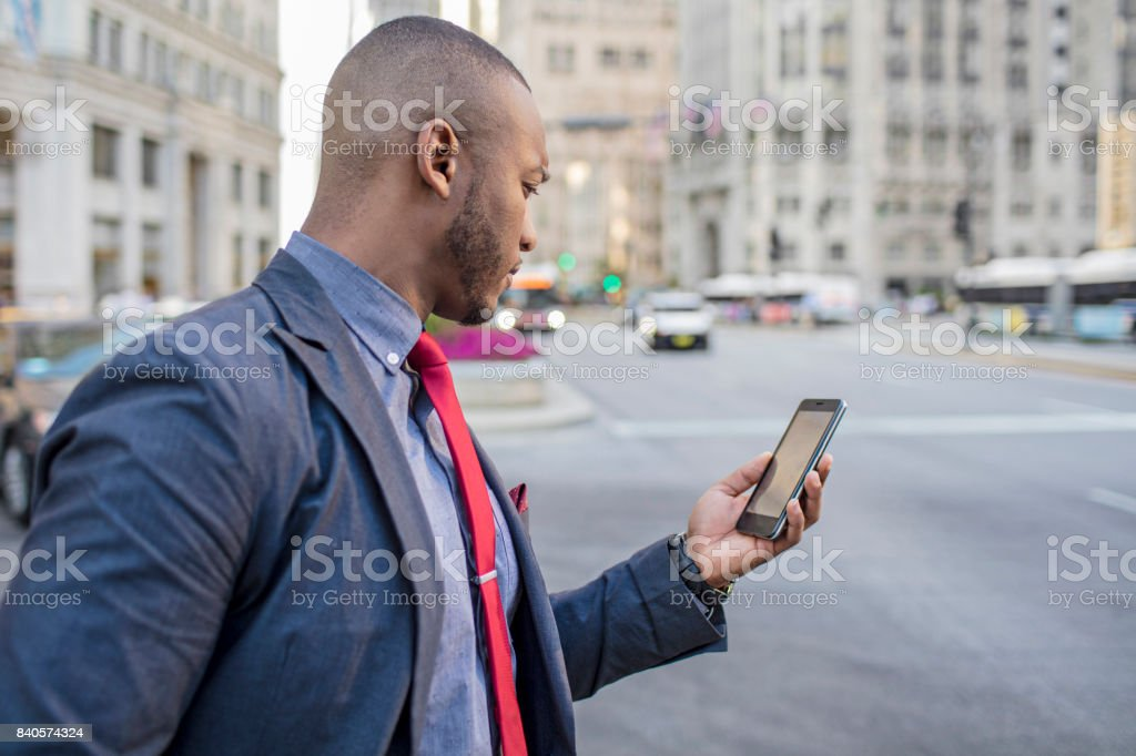 Businessman using taxi app in downtown Chicago stock photo