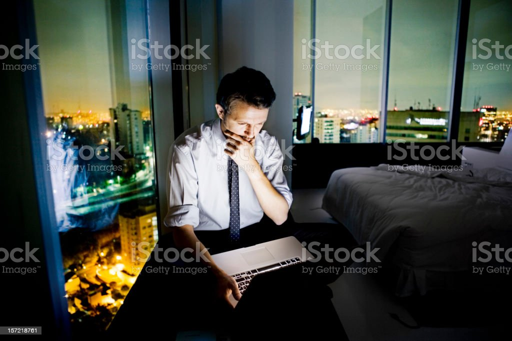 Businessman using the internet in hotel room stock photo