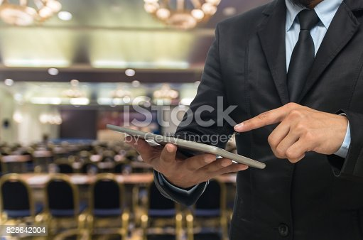 istock Businessman using the tablet on the Abstract blurred photo of conference hall or seminar room background 828642004