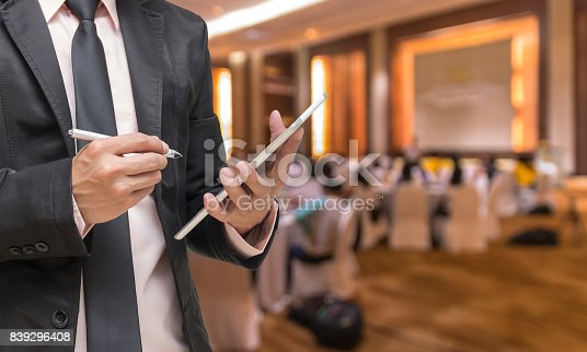 istock Businessman using the tablet on the Abstract blurred photo of conference hall or seminar room with attendee background 839296408