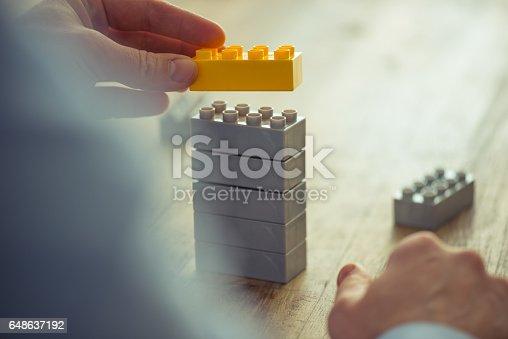 istock Businessman using toy building blocks 648637192