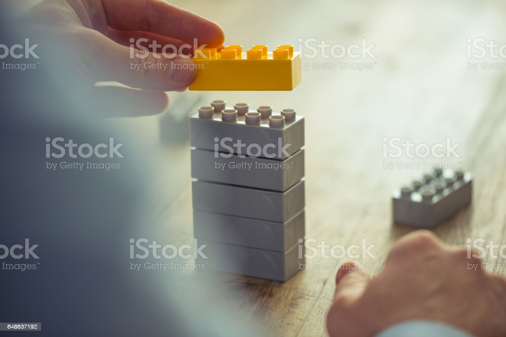 Businessman using toy building blocks stock photo