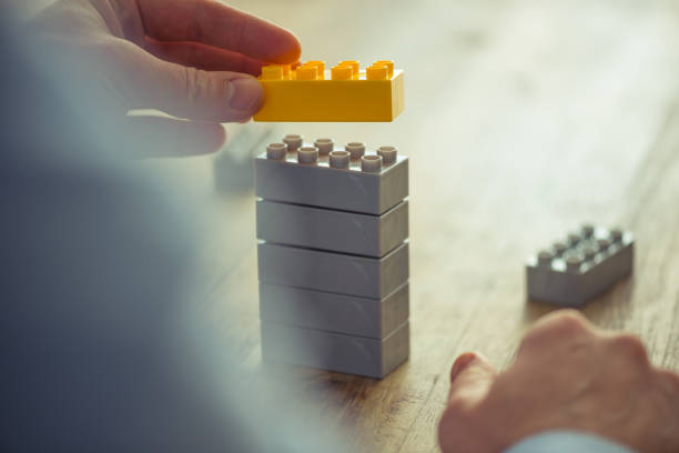 businessman using toy building blocks - development stock photos and pictures