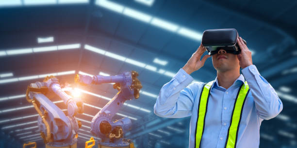 Businessman using VR Glasses for virtual reality and robot welding machines stock photo