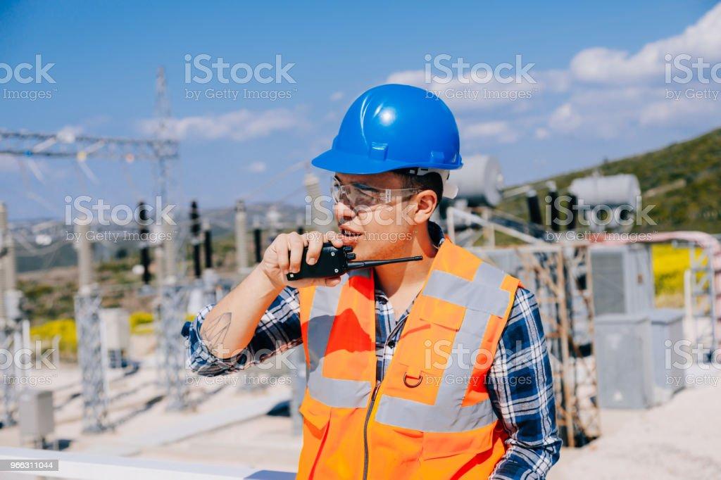 Businessman using walkie-talkie against power plant stock photo