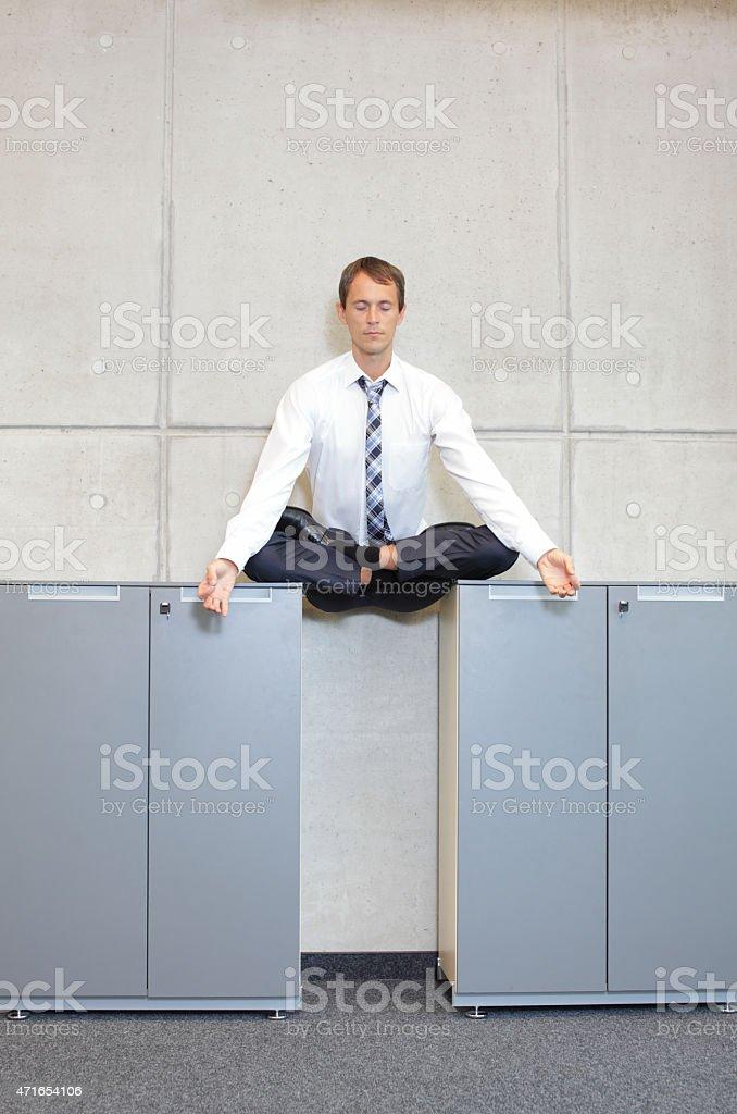 businessman v3.0 - meditating in lotus pose in office stock photo