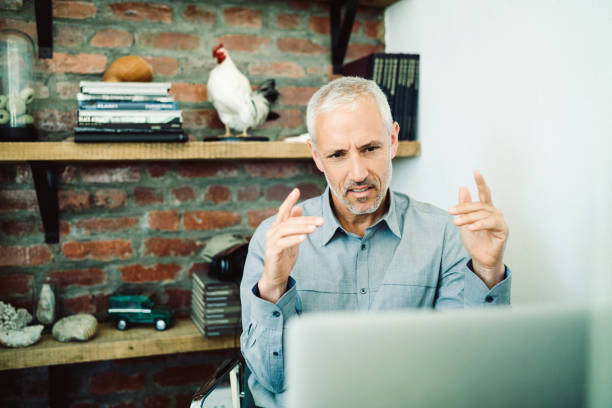 Businessman video conferencing while gesturing stock photo