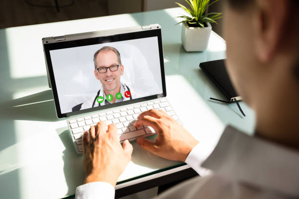 businessman videoconferencing with doctor on laptop - telemedicine stock pictures, royalty-free photos & images