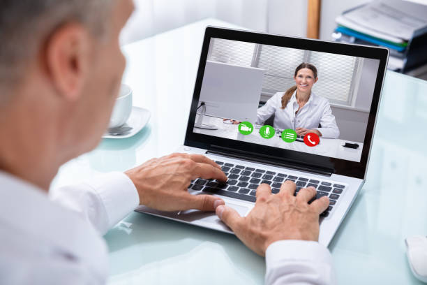 Businessman Videoconferencing With Doctor On Laptop stock photo