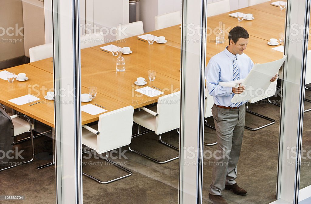 Businessman viewing blueprints at conference room window royalty-free stock photo