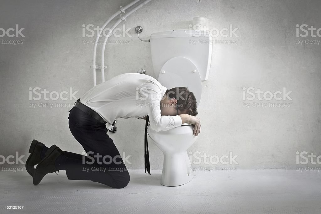 Businessman vomiting in toilet in concrete room stock photo