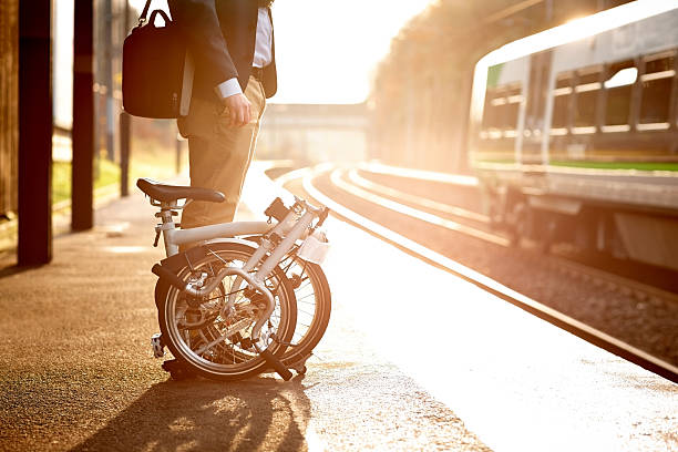 Businessman waiting at railway station platform Cropped image of businessman with his folding bicycle waiting for his train at railway station platform foldable stock pictures, royalty-free photos & images