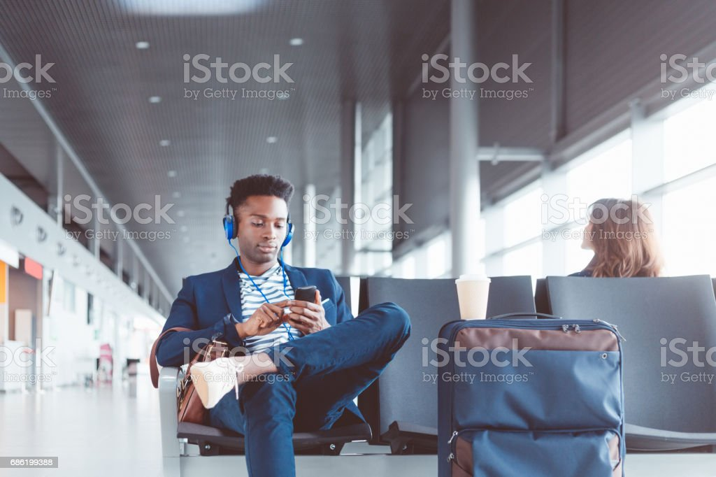 Businessman waiting at the airport lounge listening music stock photo