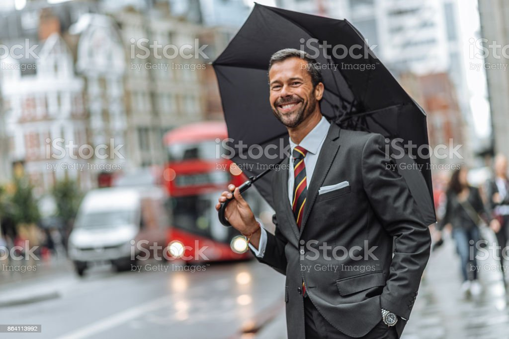Businessman waiting for bus on bus stop in London royalty-free stock photo