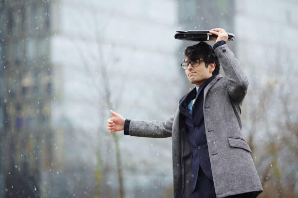 homme d'affaires attendant pour le taxi dans la neige - homme faire coucou voiture photos et images de collection