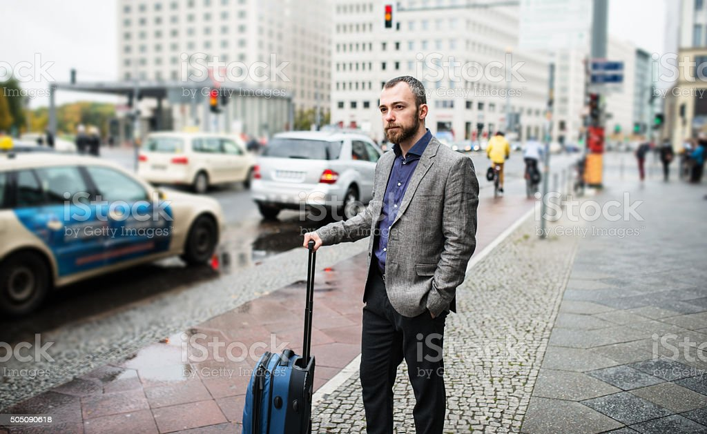 businessman waiting the taxi on the street of berlin stock photo