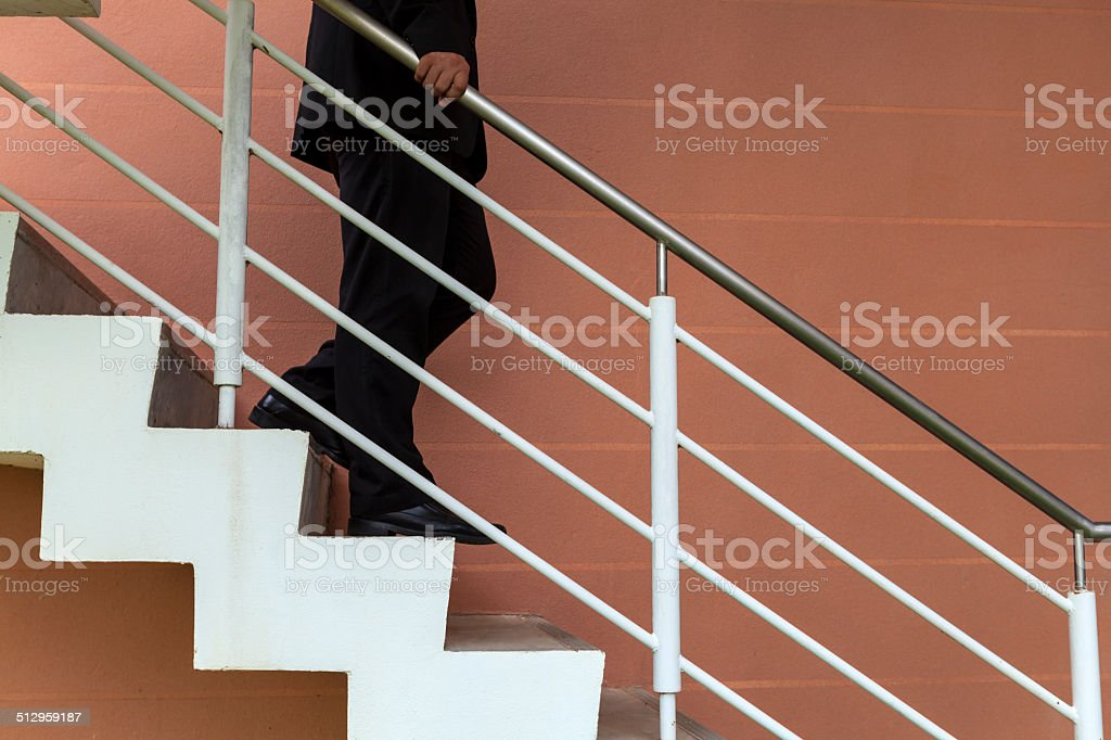 businessman walk down stair, demote,demote,suppress, defame stock photo
