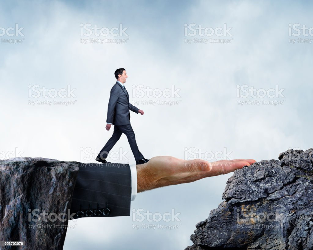 Businessman Walking Across Bridge Created By Large Hand stock photo