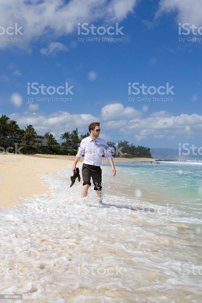 Businessman Walking Along the Beach royalty-free stock photo
