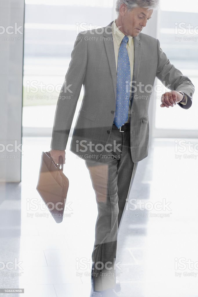 Businessman walking and checking the time on wristwatch royalty-free stock photo