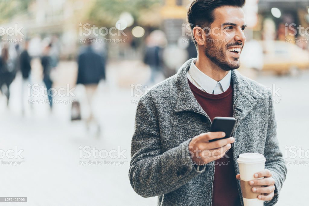 Businessman walking on the street, drinking coffee and using a smart...