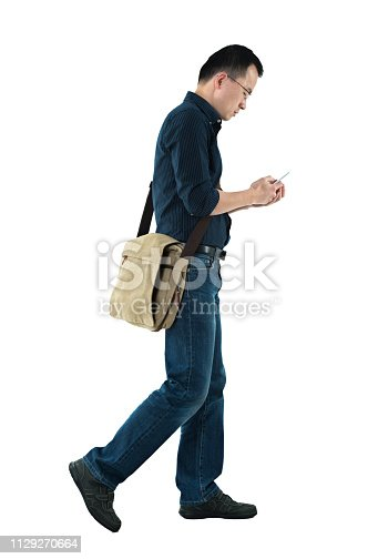 istock Businessman walking and using mobile phone 1129270664