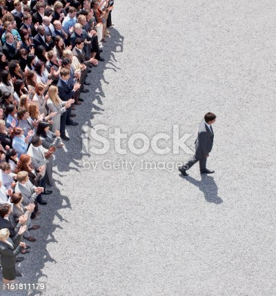 istock Businessman walking away from clapping crowd 151811179