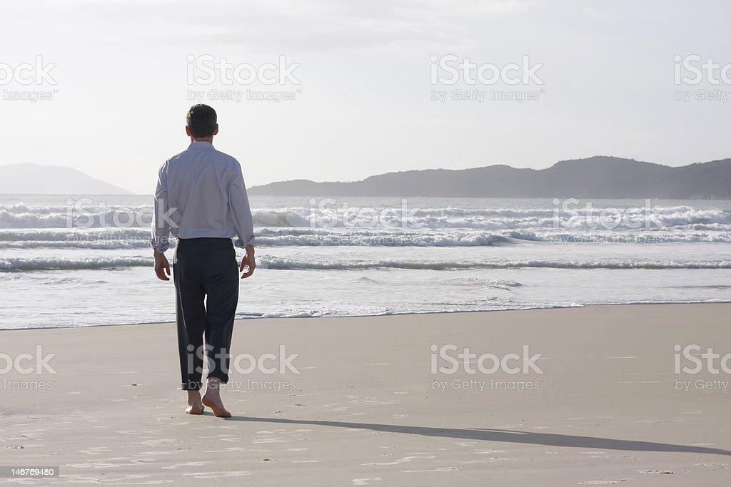 Businessman walking barefoot on a beach stock photo
