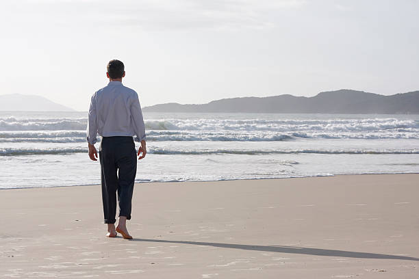 Businessman walking barefoot on a beach stock photo