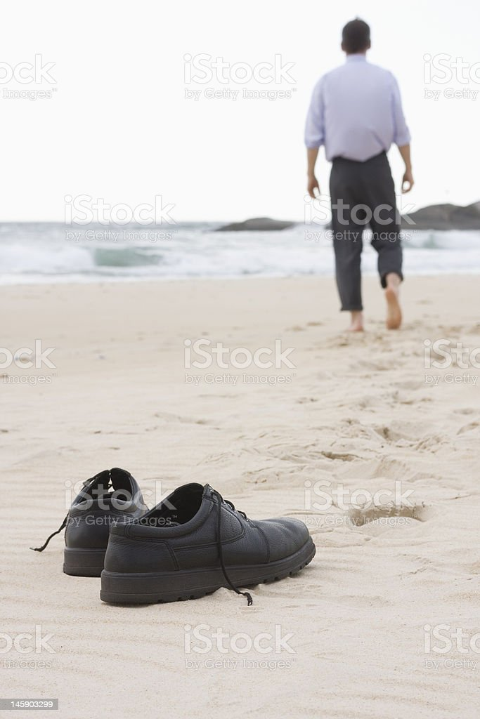 Businessman walking barefoot on beach stock photo