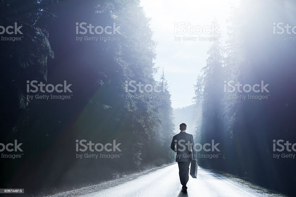 Businessman Walking Down Middle Of Road stock photo