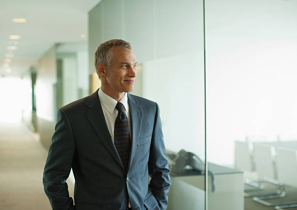 Businessman walking down modern office corridor stock photo