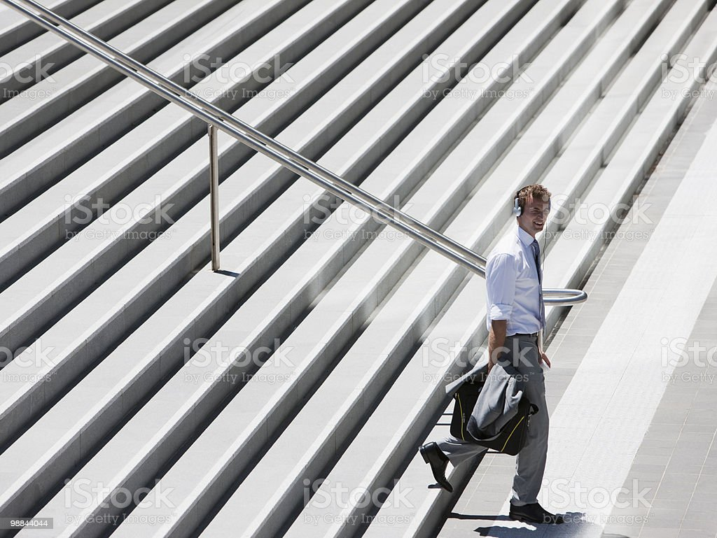 Businessman walking down steps outdoors royalty free stockfoto