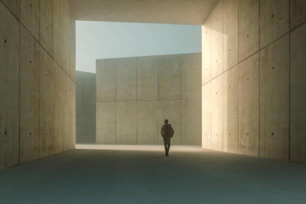 Businessman walking in concrete corridor stock photo