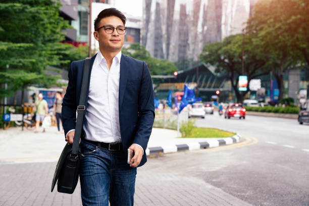 businessman walking in downtown kuala lumpur malaysia - asia stock pictures, royalty-free photos & images