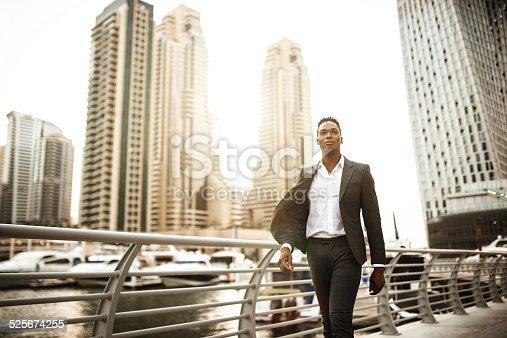 istock Businessman walking in dubai marina 525674255