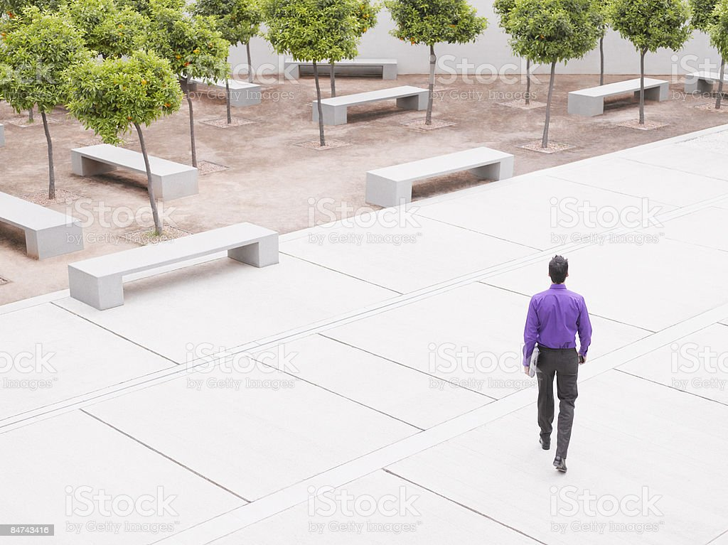 Businessman walking in modern courtyard stock photo