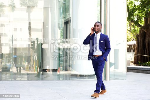 istock Businessman walking in the city using mobile phone 513483300
