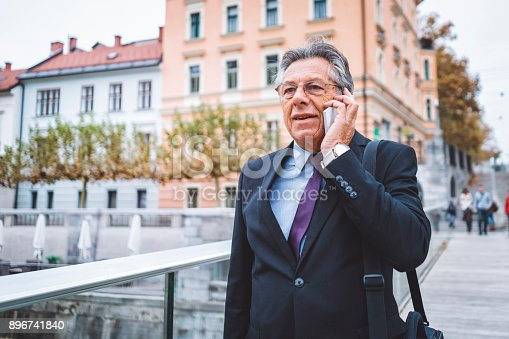 istock Businessman walking in the city using mobile phone 896741840