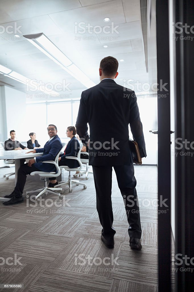 Businessman walking into a meeting room stock photo