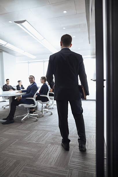 Businessman walking into a meeting room Businessman walking into a meeting room governing board stock pictures, royalty-free photos & images