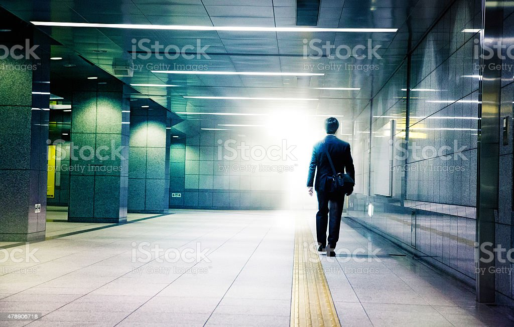 Businessman walking into the light end of tunnel stock photo