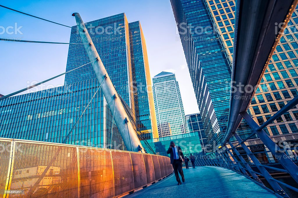 Businessman walking on a contemporary bridge in Canary Wharf, London stock photo